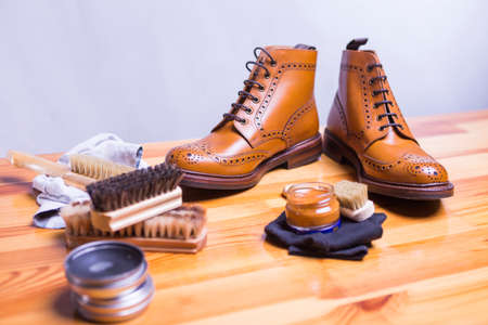 Footwear Ideas and Concepts. Close-up of Premium Tan Brogue Leather Boot with Set of Cleaning Accessories,Wax  and Cloth.Focus on Shoes.Horizontal Image