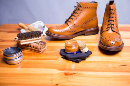 Footwear Ideas and Concepts. Close-up of Premium Tan Brogue Leather Boot with Set of Cleaning Accessories,Wax, Cloth.Horizontal Orietnation Stock Photo