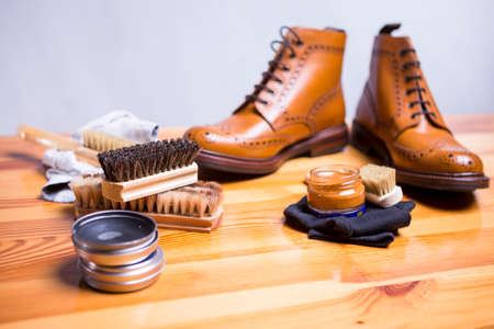 Footwear Ideas and Concepts. Close-up of Premium Tan Brogue Leather Boot with Set of Cleaning Accessories,Wax  and Cloth.Focus on Brush and Bristles.Horizontal Image