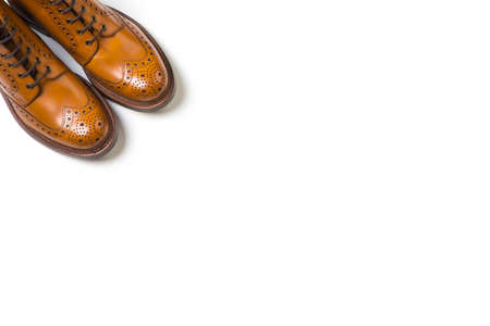 Footwear Ideas. Pair Of Separate Luxury Tan Brogue Boots On Pure White Background with Copy Space.Horizontal Image Composition