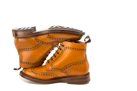 Footwear Ideas. Premium Tanned Brogue Derby Boots Made of Calf Leather with Rubber Sole. Turned Over Each Other. Isolated Over Pure White Background.Horizontal Image