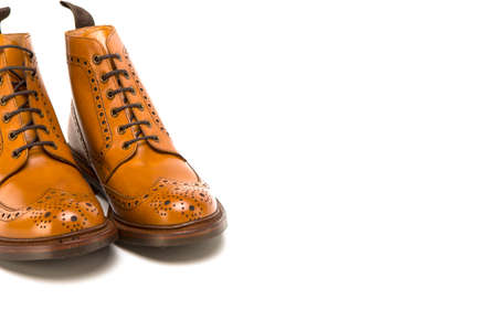 Male Footwear Ideas. Closeup of Pair of  Premium Tanned Brogue Derby Boots Made of Calf Leather with Rubber Sole. Isolated Over Pure White Background. Horizontal Orientation Stock Photo
