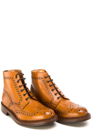 Footwear Ideas. Premium Tanned Brogue Derby Boots Made of Calf Leather with Rubber Sole. Isolated Over Pure White Background. Vertical Image Stock Photo
