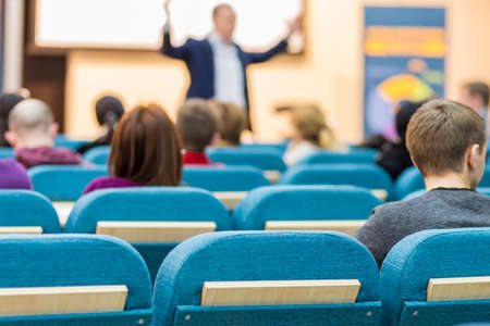 Business Meetings Concepts and Ideas. Mature Experessive Male Presenter Speaking in Front of the Group Of Young Listeneres During a Conference.Horizontal Image Orientation