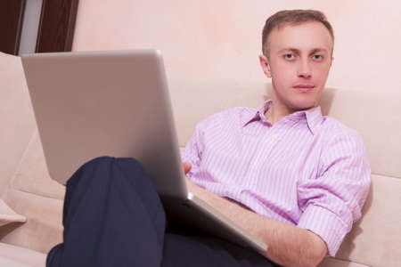 Youth Concepts and Ideas. Handsome Man in Business Style Clothing Sitting on Couch while Legs Folded. Posing with Laptop Computer. Horizontal Image Composition