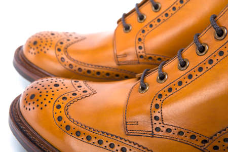 Extreme Closeup of Mens Tanned Brogue Leather Boots with Rubber Sole. Isolated Over White Background.Horizontal Image