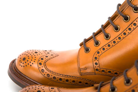 Extreme Closeup of Mens Tanned Brogue Leather Boots with Rubber Sole. Isolated Over White Background.Horizontal Image Orientation Stock Photo
