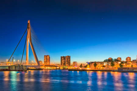 Travel Concepts. View of Unique and Beautiful Erasmus Bridge in Rotterdam. City Scyline on the Background. Shot Made During Blue Hour.Horizontal Image Orientation Stock Photo