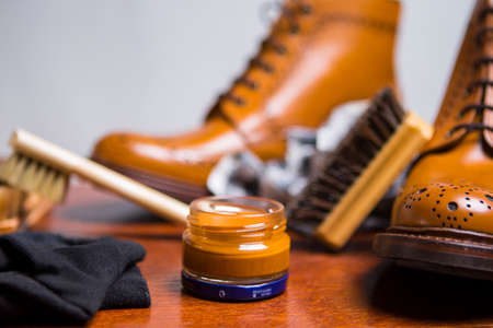 Footwear Concepts and Ideas. Extreme Closeup of Premium Male Brogue Tanned Boots with Lots of Cleaning Accessories on Foreground.Horizontal Image Orientation Stock Photo