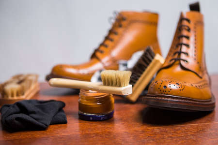 Footwear Concepts and Ideas. Premium Male Brogue Tanned Boots with Lots of Cleaning Accessories on Foreground.Horizontal Image Composition