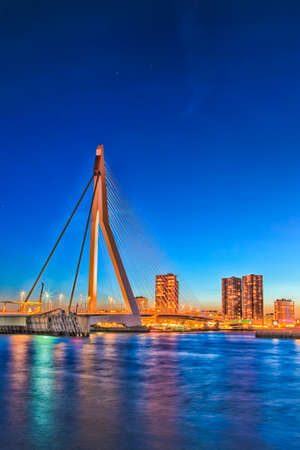 Travel Concepts. View of Unique and Beautiful Erasmus Bridge in Rotterdam. City Scyline on the Background. Shot Made During Blue Hour.Vertical Composition Stock Photo