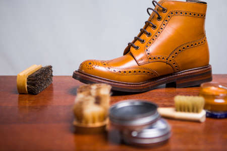 Footwear Ideas. Closeup of Premium Male Brogue Tanned Boots with Lots of Cleaning Accessories on Foreground.Horizontal Shot