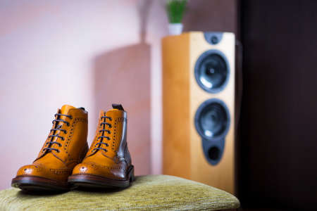 Closeup of Pair of Mens Tanned Semi-Brogue Boots on Soft Surface Placed Indoors. Against of Floorstanding Loudspeaker on Background.Horizontal Image