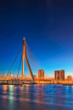 Travel Concepts. View of Unique and Beautiful Erasmus Bridge in Rotterdam. City Scyline on the Background. Shot Made During Blue Hour.Vertical Image Orientation