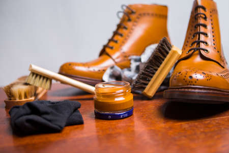 Footwear Concepts and Ideas. Premium Male Brogue Tanned Boots with Lots of Cleaning Accessories on Foreground.Horizontal Shot