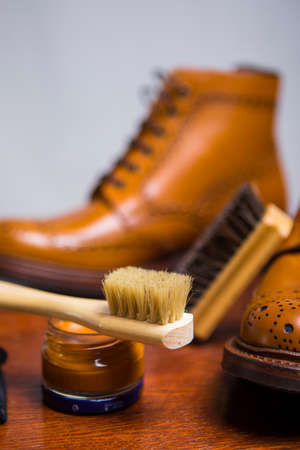 Footwear Concepts and Ideas. Closeup of Premium Male Brogue Tanned Boots with Lots of Cleaning Accessories on Foreground.Vertical Image Stock Photo