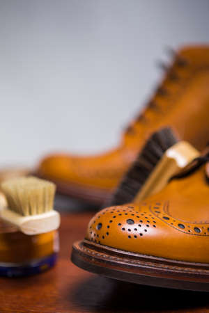 Footwear Concepts and Ideas.Extreme Closeup of Tips of Premium Male Brogue Tanned Boots with Lots of Cleaning Accessories on Foreground.Vertical Image Stock Photo