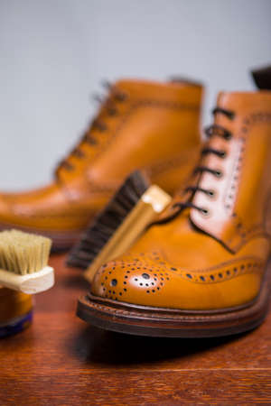 Footwear Concepts and Ideas. Closeup of Premium Male Brogue Tanned Boots with Lots of Cleaning Accessories on Foreground.Vertical Image Composition Stock Photo