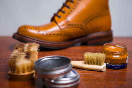 Footwear Ideas. Closeup of Premium Male Brogue Tanned Boots with Lots of Cleaning Accessories on Foreground.Horizontal Image