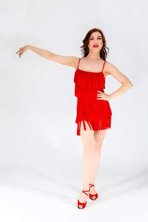 Ballroom Dances Project. Full Length Portrait of Female Ballroom Dancer in Red Flowing Latin American Dress On White. Demonstrating Cha-Cha Dance.Vertical Shot Stock Photo