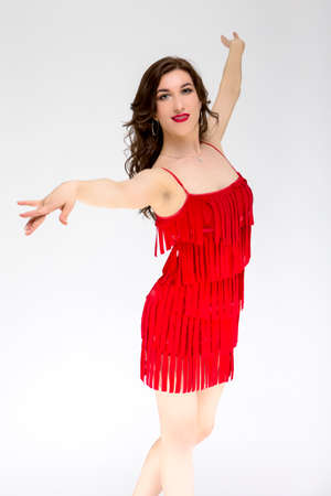 Ballroom Dances Project and Ideas. Portrait of Female Ballroom Dancer in Red Flowing Latin American Dress Against White. Demonstrating Rumba Dance. Vertical Image Orientation