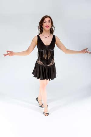 Ballroom Dances Concepts. Portrait of Female Ballroom Dancer in Black Latin American Dress Against White. Demonstrating Samba Position.Vertical Image Orientation