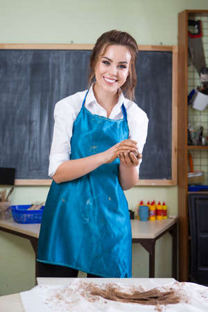 Pottering and Clay Making Concepts. Happy Smiling Female Professional Worker in Apron Preparing a Piece of Clay in Professional Workshop.Vertical Image Orientation Stok Fotoğraf