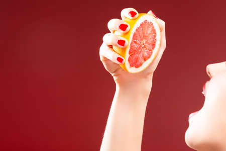 Passion Fruit Series. Closeup of Hand of Caucasian Girl Squeezing Grapefruit Half To Her Mouth. Against Red Background. Horizontal Image Composition