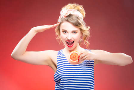 Fresh Fruit Ideas. Smiling Sensual Caucasian Blond With Two Grapefruit Slices in Front Saluting. Against Red Background. Horizontal Image Orientation
