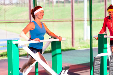 Sport Concepts. Portrait of Two Active Sportive Females Training Outdoors on Stepper Trainer. Horizontal image Orientation Stock Photo