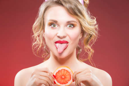 Fruit Ideas. Funny Sexy Caucasian Blond Girl With Grapefruit Slice in Front of Face. Showing Tongue. Against Red Background.Horizontal Image