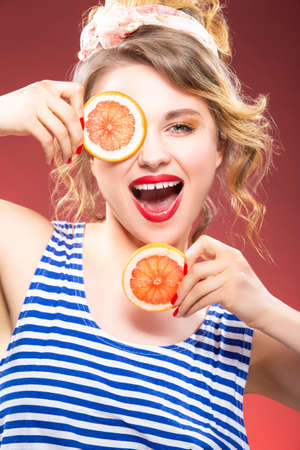Fruit Concepts and Ideas. Smiling Passionate Caucasian Blond With Two Grapefruit Slices in Front of Face. Against Red Background. Vertical Image Composition Banco de Imagens
