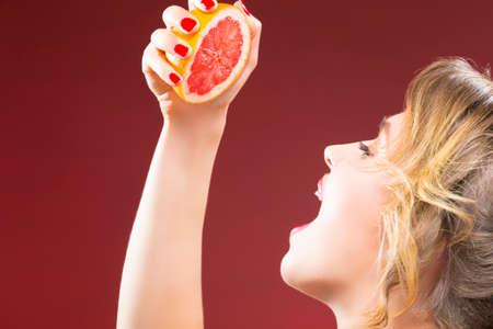 Passion Fruit Series. Closeup of Hand of Caucasian Girl Squeezing Grapefruit Half To Her Mouth. Against Red Background. Horizontal Image