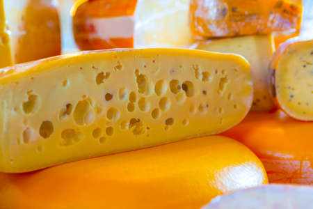Vegan eating Ideas and Concepts. Closeup of Traditional Dutch Cheese Cut in Two halves On Market Display.Horizontal Image