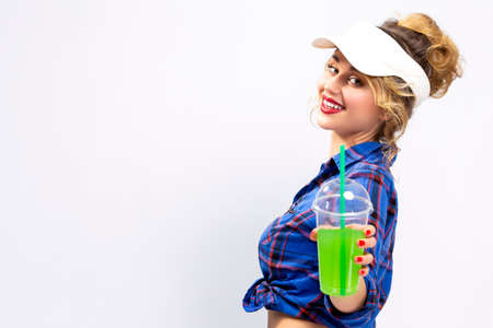 Youth Ideas and Concepts.Closeup of Enticing Caucasian Female in Checked Shirt Offering Green Cocktail Towards Viewer. Against White Background.Horizontal Image