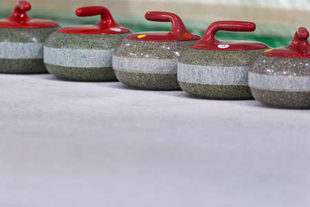 Sport Concepts. Closeup of Curling Red Handle Stones on Ice.Horizontal Image Composition