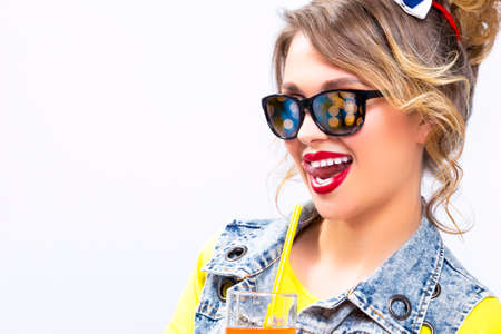 Happy Life Ideas and Concepts. Upbeat and Happy Caucasian Blond Girl With Orange Juice and Straw. Wearing Denim Vest and Sunglasses. Against White. Horizontal Image