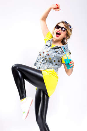 Happy Youth Lifestyle Concepts. Closeup of Upbeat Caucasian Blond Girl Dancing With Cup of Blue Cocktail. Wearing Denim Vest and Sunglasses.Vertical Image Orientation Stock Photo