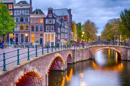 Nachtzicht van het stadsgezicht van Amsterdam met zijn grachten. Verlichte brug en traditionele Nederlandse huizen bij schemering op de achtergrond. Horizontaal schot Stockfoto