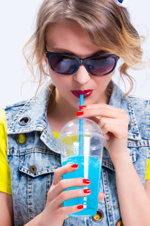 Happy Youth Lifestyle Concepts. Closeup of Upbeat Caucasian Blond Girl Drinking Blue Cocktail Through The Straw. Wearing Denim Vest and Sunglasses.Vertical Image Orientation