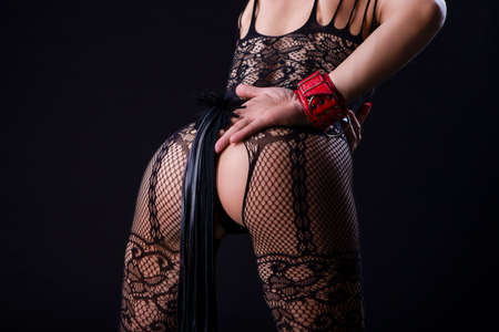 BDSM Ideas. Back View of Caucasian Woman in Sexy Lingerie Posing with Leather Lash for BDSM Role Game.In red Handcuffs. Horizontal Image 免版税图像