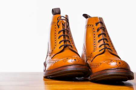 Footwear Concepts.Pair of High Gentleman Tanned Brogues Boots. Isolated Over White Background.Horizontal Composition
