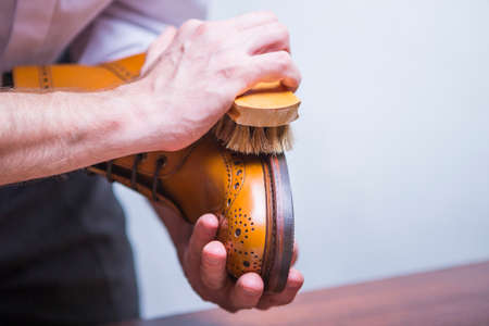 Footwear Concepts. Closeup of Male Hands with Polishing Brush for Tan Brogue Derby Boots. Horizontal Image Composition