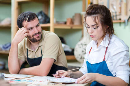 Happy Caucasian Ceramists Glazing and Painting Ceramic Clay Tiles in Workshop Together. Horizontal image Stock Photo