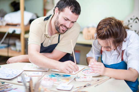 Pottering Ideas. Two Young Caucasian Ceramists Painting and Glazing Clay Crafts Together in Workshop Using Paintbrushes. Horizontal Image Stock Photo