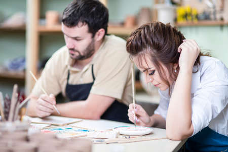 Two Young Caucasian Ceramists Painting and Glazing Clay Crafts Together in Workshop with Paintbrushes.Horizontal Image