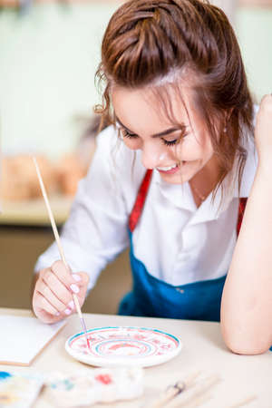Young and Happy Female Ceramist Using Paintbrush For Glazing and Painting Ceramic Crafts in Studio. Vertical image Orientation