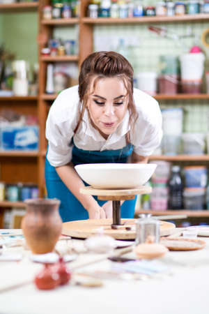 Portrait of Professional Female Ceramist in Apron Glazing Ceramic Bowl on Turntable in Workshop. Blowing Flour Dust from Surface.Vertical Image Orientation Stock Photo