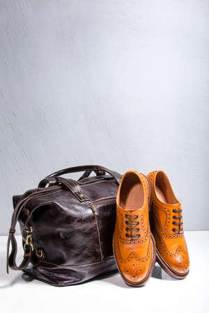 Footwear and Accessories Concepts. Male Tanned Full Broggued Oxford Calf Leather Shoes Along With Dakr Brown Leather Travel Bag on White. Vertical Orientation