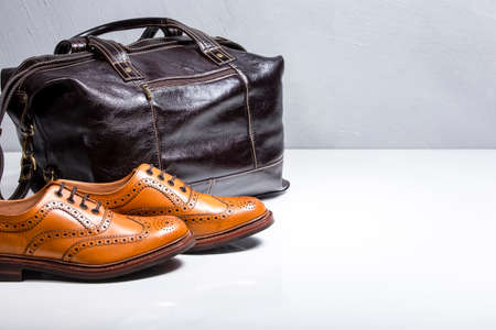 Male Tanned Full Broggued Oxford Calf Leather Shoes Along With Dakr Brown Leather Travel Bag on White Surface. Horizontal Image Orientation Stock Photo